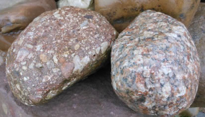 shows two erratics of similar size and colour, but the one on the left is made from rock fragments and is sedimentary, while that on the right has interlocking crystals and is igneous.