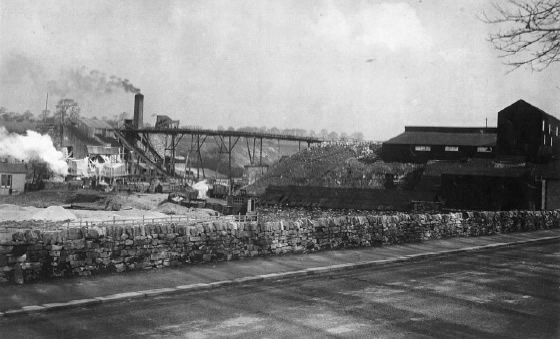 Photograph of the Bellman lime kilns in operation. The long bridge-like structure supported an endless chain conveyor which carried limestone and fuel to the top of the bank of kilns (which is to the left of the chimney).